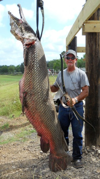 Crawford stands next to his giant alligator gar
