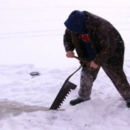 Don Fillmore of Coleman uses a 75-year-old ice saw to cut a spearing hole in Michigan ice; chain saws are also often used. Image by Steve Griffin