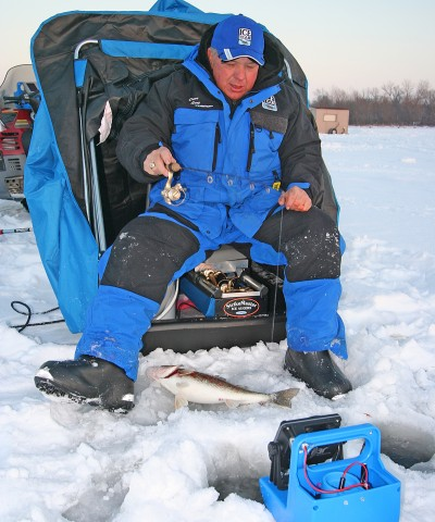 """With one nice walleye flopping on the ice, Dave Genz is back down looking for more, aggressively pounding his lure. Rather than slowing down when a fish shows up, in an effort to """"feed it,"""" Genz says we should keep a hard-pounding cadence going, and force the fish to strike."""