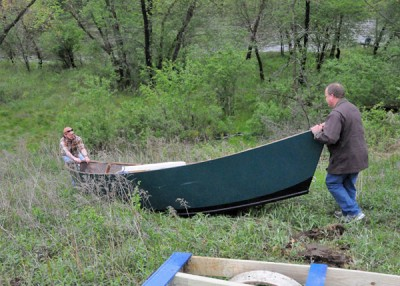 Dave, left, and Ron Bakken push their homemade drift boat toward the Eau Claire River in western Wisconsin.