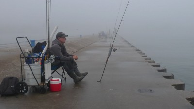 Tyler Harmon of Eau Claire, Michigan is an experienced, well-geared pier angler. Here he waits for a summer steelhead to take a bobber down.