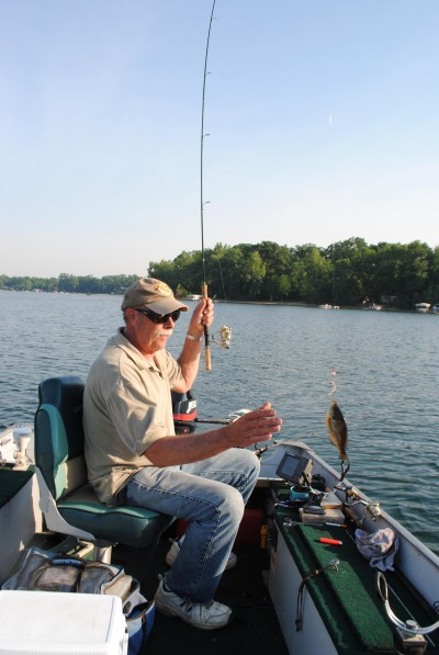 Denny Hettig swings a bluegill, caught on a Bo's Bluegill Buster, into the boat.