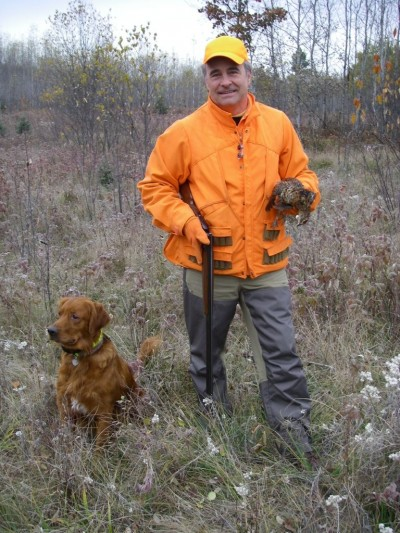 Jerry Dennis poses with a grouse retrieved by Gabe the golden retriever.