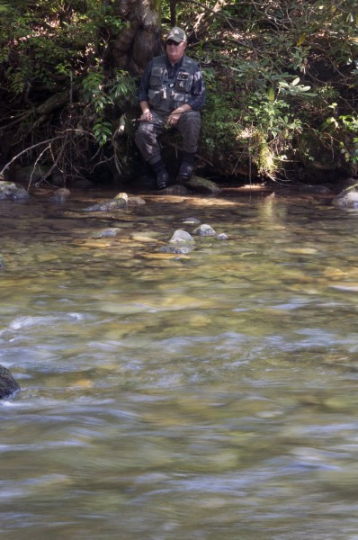 Arthur Farrell takes a break from fishing along a bank of the Davidson River.