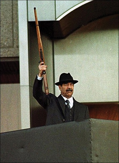Saddam Hussein carries his Ruger M77 in one of the most well-known images of the Iraqi dictator.