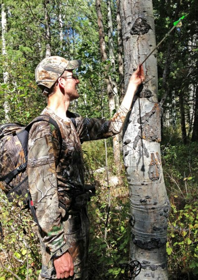 Chris White examines his arrow after missing a shot in the final hour of his weeklong bowhunt.