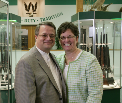 Miles hall poses with his wife at H&H Shooting Sports.