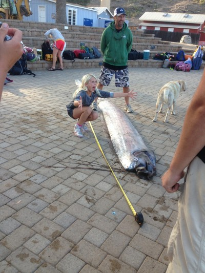A CIMI student poses with the large oarfish.