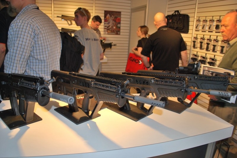 """A line of """"ban-compliant"""" Tavors at the IWI US SHOT Show booth."""