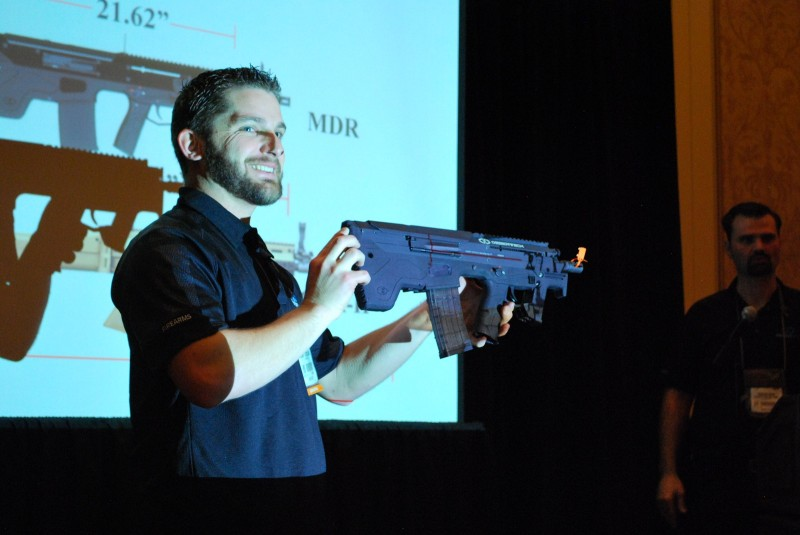 A smiling Desert Tech employee holds up the .223 MDR-C for display.