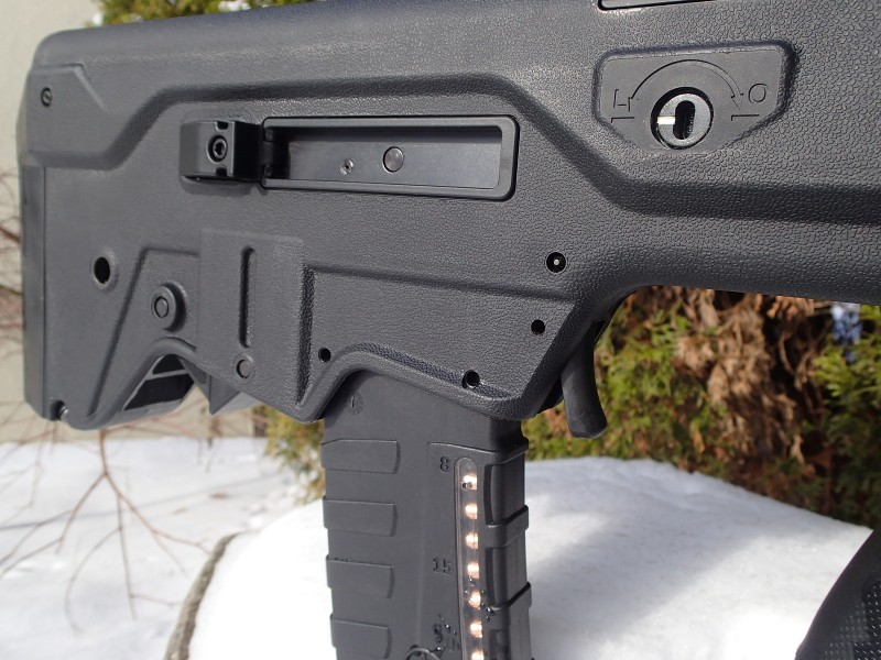 "Some of the Tavor's controls are fully ambidextrous. Seen  here are the magazine release ""trigger"" (located just in front of the magazine) and the bolt release (which can be seen just barely peeking out behind the magazine). Note also the two locking pins for the trigger mechanism."