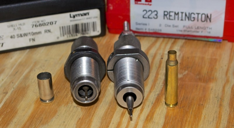 A .40 S&W resizing die (left) Note the carbide ring. The .223 Remington resizing die on the right has the decapping rod extended to show the case mouth expander ball.