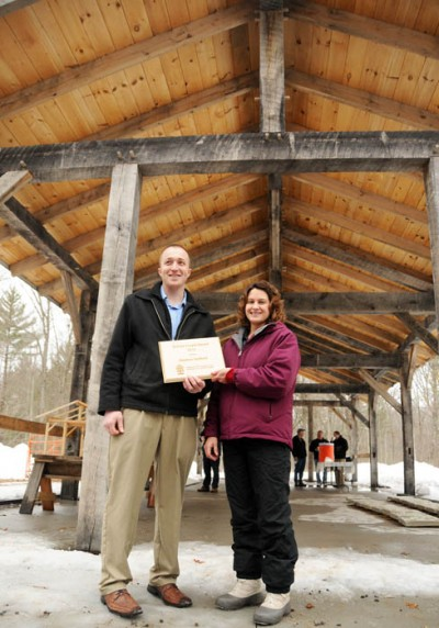 Stephen Hadfield, a tech-ed teacher at Pittsville High School in Wood County, receives a 2013 Wisconsin School Forest Award from the DNR's Gretchen Marshall for directing construction of this timber-frame shelter at the Pittsville School Forest.