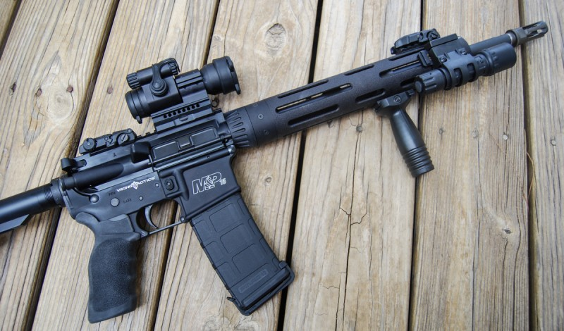 The author's first home-defense configuration of the M&P15 VTAC I, featuring a vertical foregrip, Aimpoint PRO red dot sight, and the rifle's included SureFire G2.