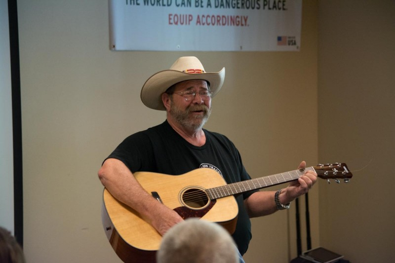 """Crimson Trace founder Lew Danielson serenades the awards banquet crowd with """"Leaving on a Jet Plane"""""""