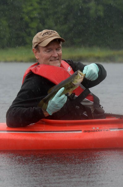 Larry Keen prepares to release a largemouth bass after catching it during a heavy downpour in Iron County on July 27.