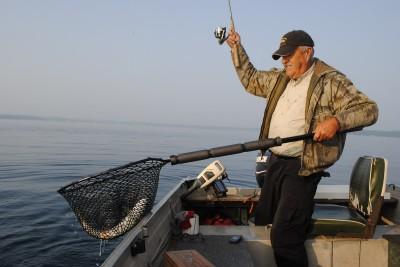 Al Scott nets a lake trout jigged out of deep water.