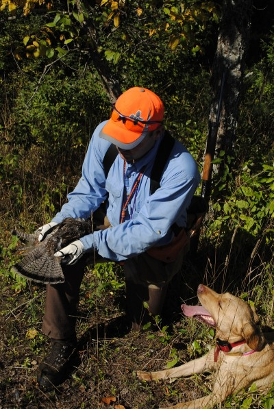 Ric Heller shows off a grouse to his Lab.
