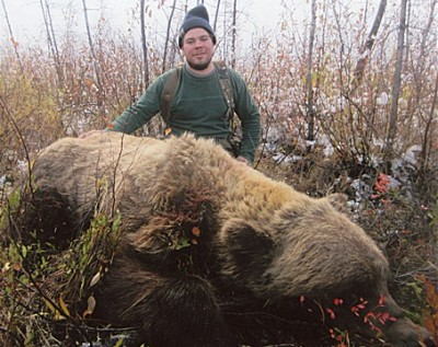Larry Fitzgerald poses with the largest grizzly bear taken by a hunter. It was bagged in 2013 near the Totatlanika River, Alaska.