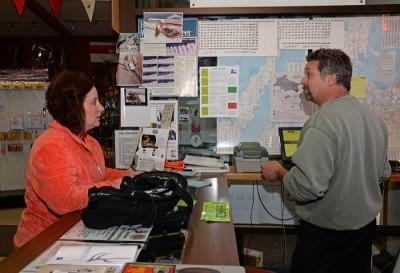 Michelle Kasten, Luxemburg, buys her family's deer licenses from Lee Simonar, owner of Lee's Sports.