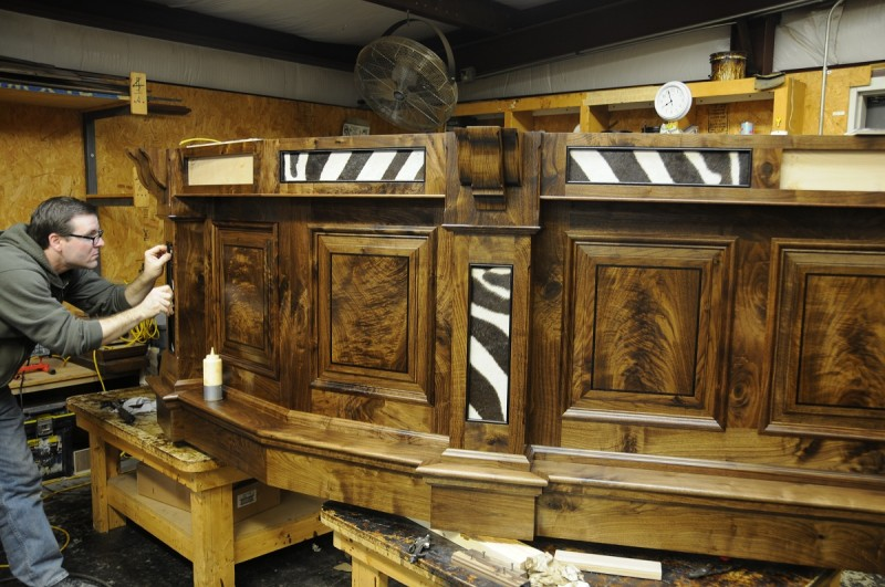 A craftsman at Julian & Sons builds a custom bar for a client trophy room.