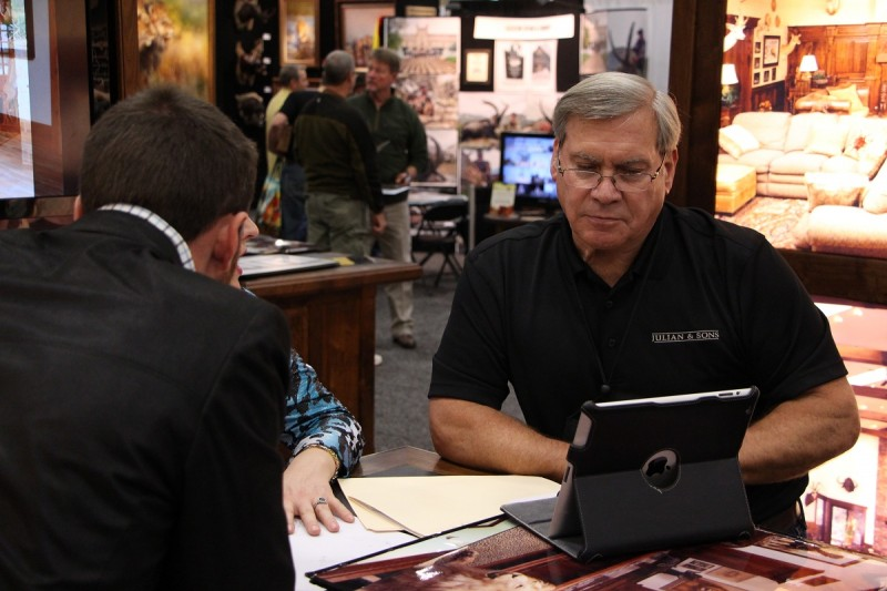 Tom Julian works with an attendee at the Dallas Safari Club convention and expo.