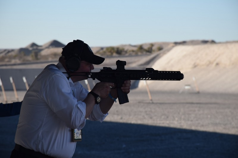 A shooter with an MCX equipped with an extended handguard and suppressor.