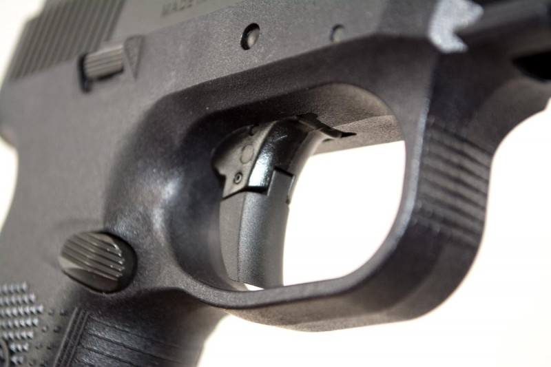The hinged trigger has a large, curved face.
