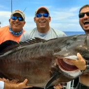 Alex Newman (center right) holds up his potential world record grouper with his crew.