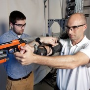 Researcher Dan Beache (right) tries out his arm exoskeleton during a shooting simulation.