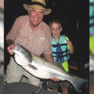 The author with his Boone Lake fishing partner, Parker. Parker's last fish of the night was a 38-inch striper. As much fun as the fishing was, Parker wasn't too keen on holding the fish.