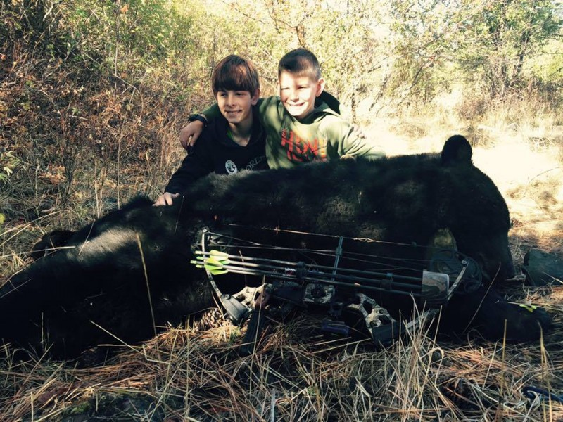 Sam Sherman (right) next to his brother Ty as they pose with his bear.