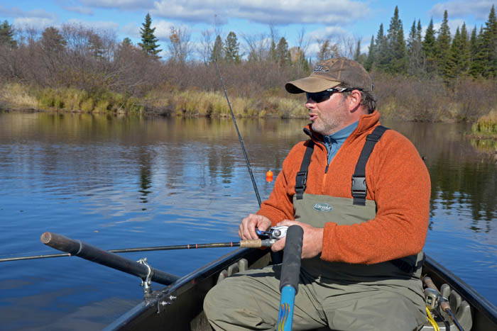 John Maier rows and fishes while drifting down a river in northwestern Wisconsin.