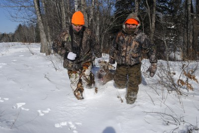 Hunters drag a deer out of the woods in Michigan.