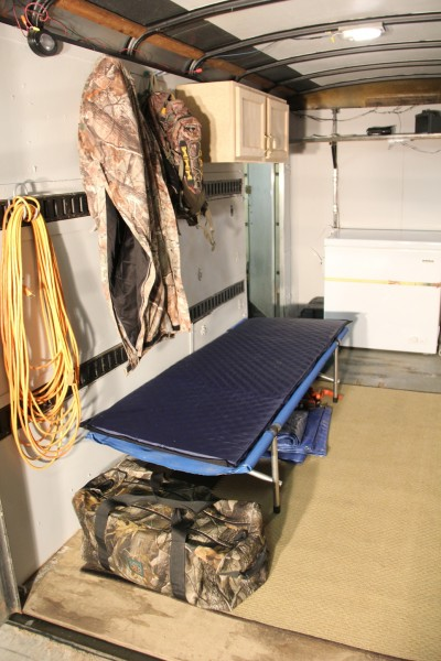 With the simple addition of a cot, I can comfortably sleep in the trailer. A small electric heater run by a generator keeps it warm.