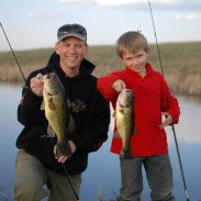 The author and his son, Luke, with a pair of South Dakota farm pond bass.