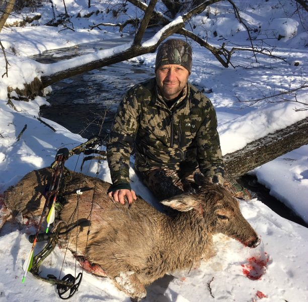 Scott Gulden with a mature doe arrowed on December 27. The deer looks wet because she died in the creek.