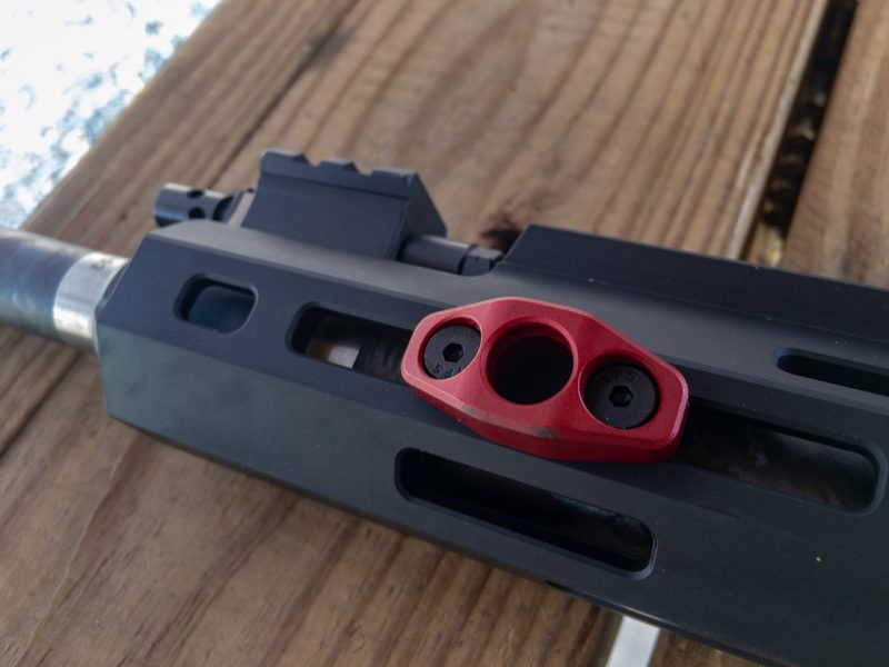 The free-floated handguard is MLOK compatible and comes with this sling attachment adapter.