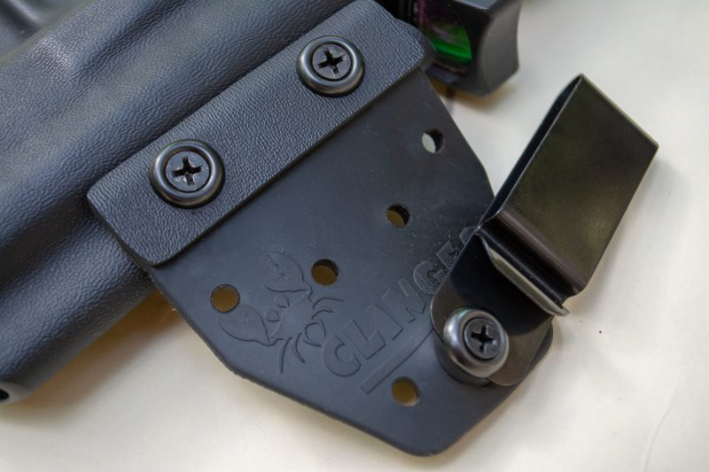 Here's the magic. The front belt clip is attached to the holster body with a flexible rubber or leather hinge. That allows the rigid back wing to draw the grip in close.